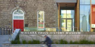 Cyclists passing the front of the Niagara Falls History Museum on Lundy's Lane