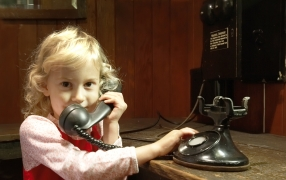 Young Homestead visitor making a phone call on a 1927 telephone.