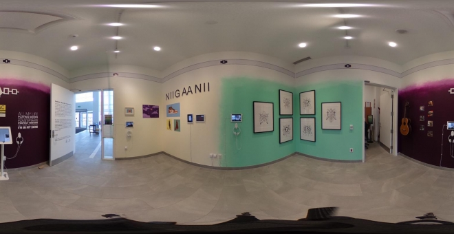 Panorama image of yellow, turquoise, and purple room with art framed on the wall