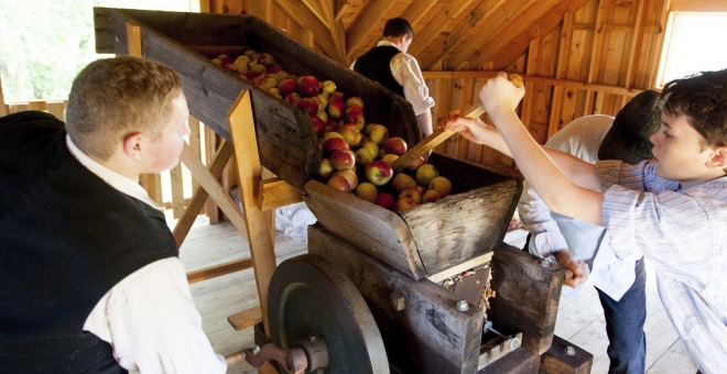 Two boys adding apples to an old-fashioned apple press