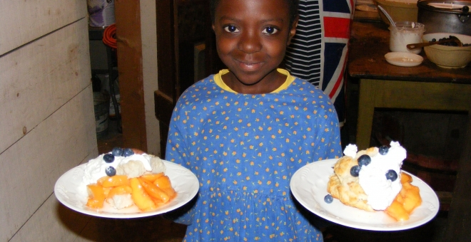 Junior volunteer with two servings of peaches on scones with whip cream and blueberries