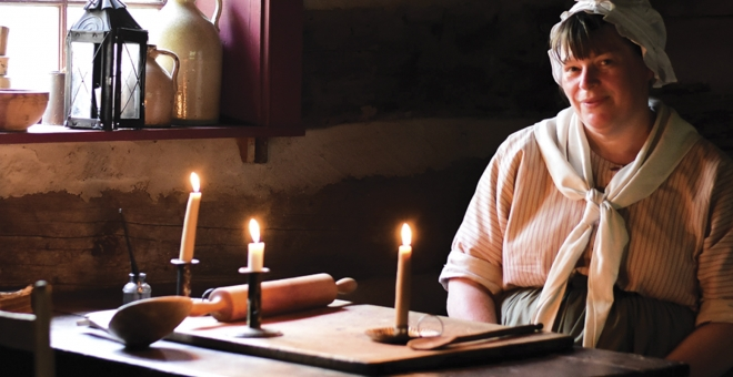 Pioneer woman in old building lit by candles