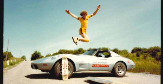 Willi Winkels jumps over a corvette before landing on a skateboard on the pavement