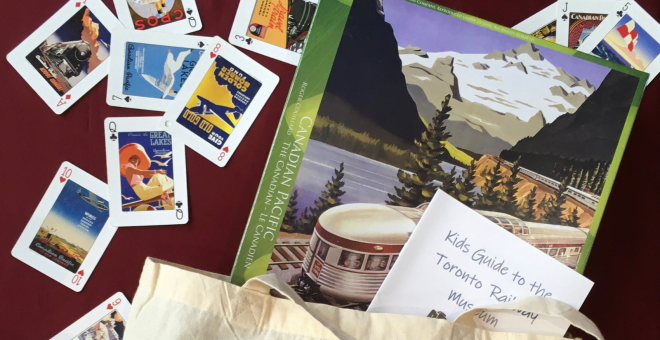 Flat-lay of a tote bag overflowing with a boxed jigsaw puzzle with a vintage Canadian Pacific Railway design, paper activity booklets, and scattered playing cards.